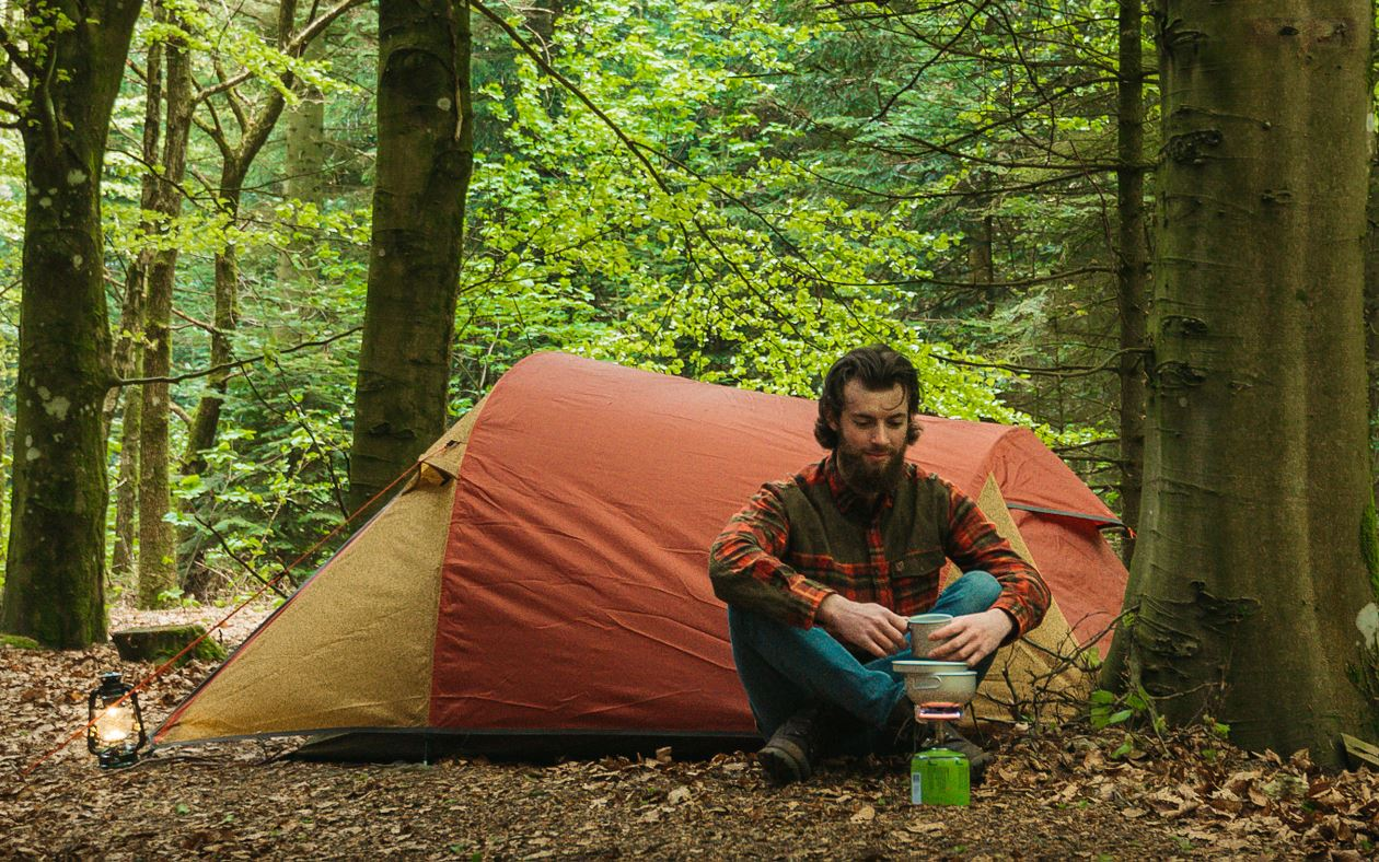 Guy camping with gas burner
