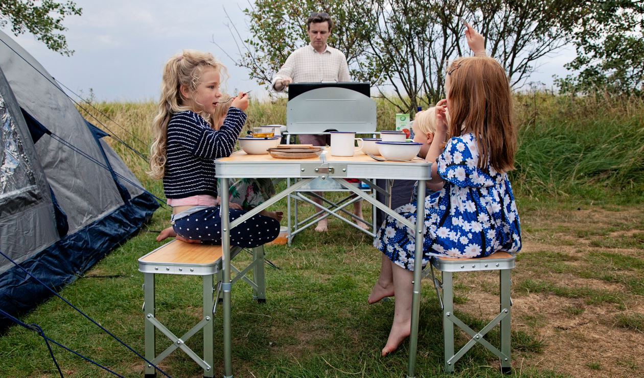 Family eating on camping furniture